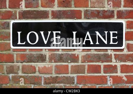 Straßenschild für Love Lane auf Ziegelmauer - Stockfoto