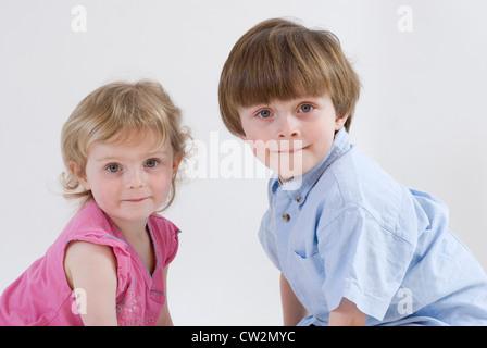 Junge und Babyschwester hocken zusammen mit Köpfen gemacht Blick in Richtung Kamera, Studioportrait Isolated on - Stockfoto