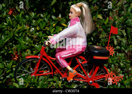 Barbie Puppe Mädchen reiten Zyklus. Spielzeug Mädchen reitet Fahrrad durch das Garten-Landschaft-Konzept von Spielzeug - Stockfoto