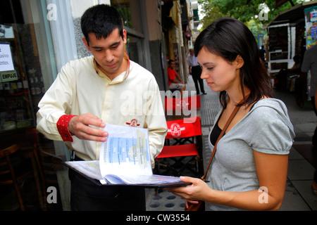 Avenida de Mayo in Buenos Aires Argentinien Sidewalk Café Restaurant Host Job Menü Fußgänger Hispanic Mann Frau - Stockfoto