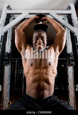 Porträt von nacktem Oberkörper junger Mann mit Hanteln trainieren - Stockfoto