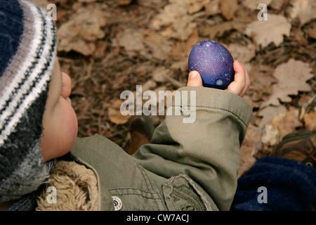 kleiner Junge hält ein Osterei in der Hand, Deutschland - Stockfoto