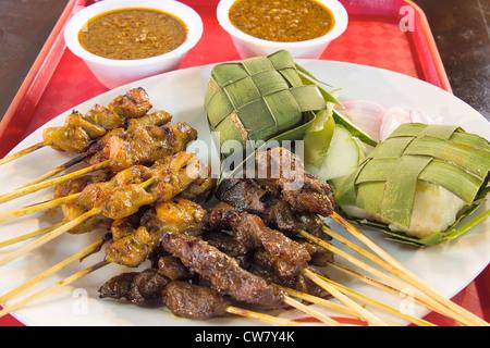Huhn, Rindfleisch und Hammelfleisch Satay mit Ketupat und Erdnuss Soße Sauce Closeup - Stockfoto