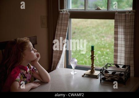 Nachdenklich Mädchen auf der Suche durch offene Fenster - Stockfoto
