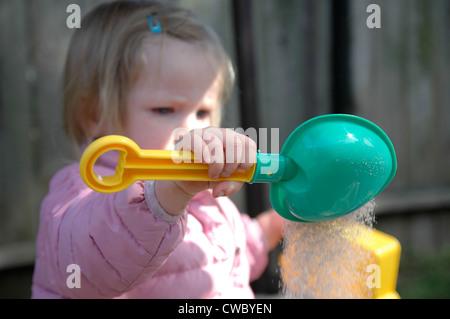 Kleinkind spielt im Sandkasten - Stockfoto