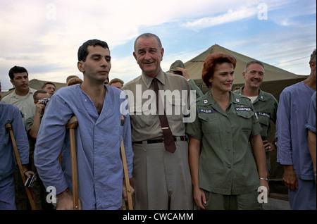 Präsident Johnson in Südvietnam. LBJ mit einem hilfsbereit verwundeten US-Soldaten und Air Force Krankenschwester - Stockfoto