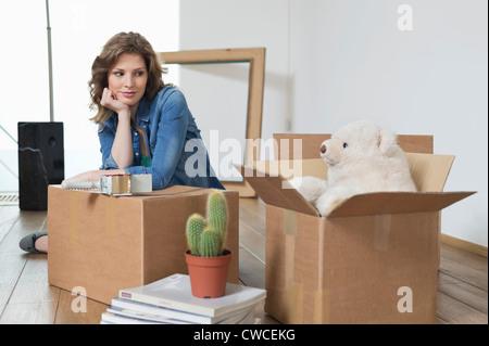Frau, stützte sich auf einen Karton und mit Blick auf ein Teddybär - Stockfoto