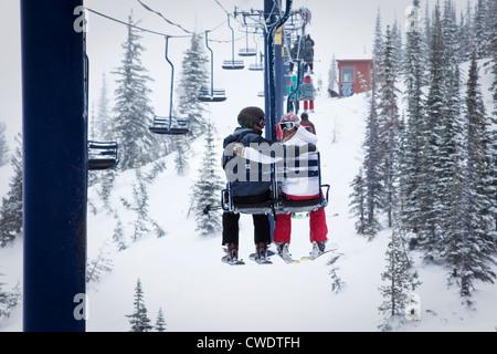 Zwei junge Erwachsene Lächeln beim Sitzen auf einer Doppel-Sessellift in einem Skigebiet in Idaho. - Stockfoto