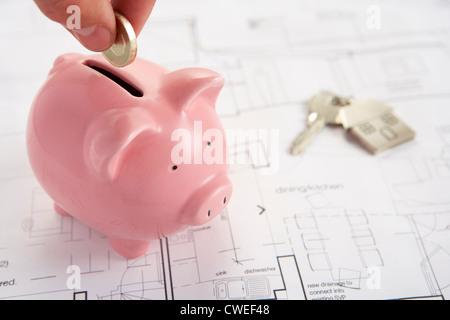 Sparschwein mit Hausplänen und Schlüsseln - Stockfoto