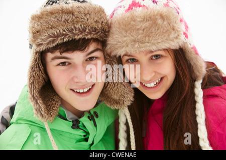 Porträt von Teenager-Paar im Schnee tragen Pelz-Hüte - Stockfoto