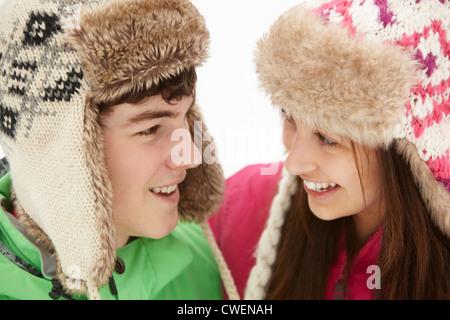 Teenager-Paar im Schnee tragen Pelz-Hüte - Stockfoto