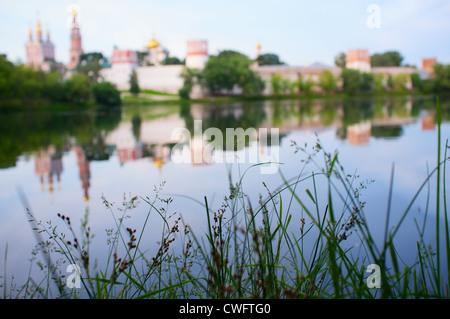 Sehen Sie am frühen Morgen Moskau Novodevichiy Kloster in Russland. Konzentrieren Sie sich auf eine Wiese. - Stockfoto