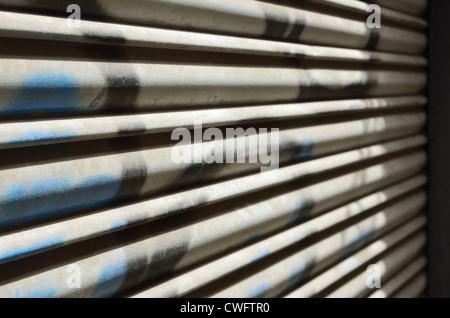 Außen Jalousie mit Streifen von Schatten und graffiti - Stockfoto