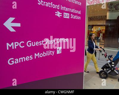 Frau schiebt Kinderwagen in der Nähe von zugänglichen Einträge für die Paralympischen Spiele 2012 in London und - Stockfoto