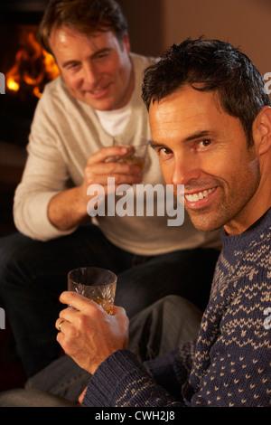 Zwei applying Männer entspannend auf Sofa trinken Whisky - Stockfoto