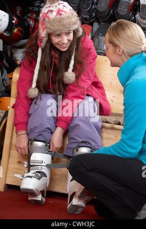 Sales Assistant hilft Teenager-Mädchen, versuchen auf Skischuhe im Verleih Shop - Stockfoto