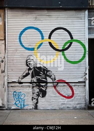 Street-Art Darstellung Jugendlicher einer der Olympischen Ringe zu stehlen - Stockfoto