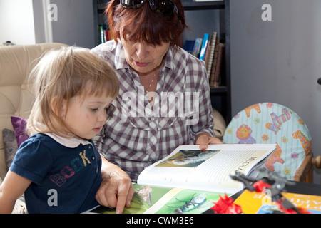 Polnische Oma (Babcia) lesen, ihr junge Enkelin Alter 63 und 2. Zawady Zentralpolen - Stockfoto