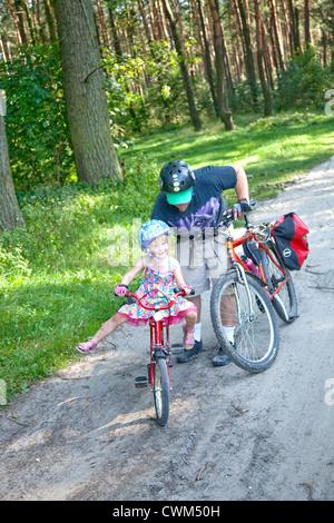 Papa geben einen Start Tochter auf Fahrrad-Balancing polnische National Forest Trail Alter 4 und 37 Protokollierung. - Stockfoto