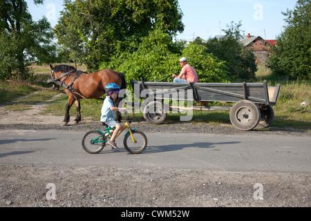 Behelmte polnischer junge mit seinem Fahrrad Dorf Gasse neben Pferd gezeichneten Wagen 4 Jahre. Mala Wola Zentralpolen - Stockfoto