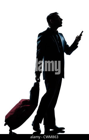 eine kaukasische Reisender Geschäftsmann zu Fuß am Telefon mit Koffer voller Länge Silhouette im Studio isoliert - Stockfoto
