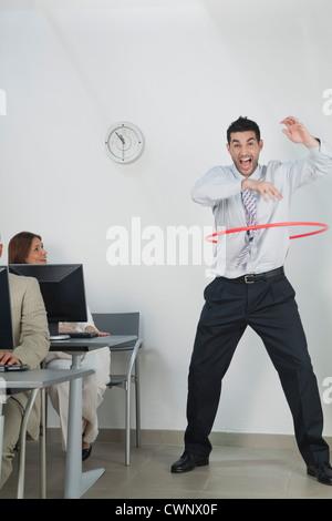 Junger Geschäftsmann mit Hula-Hoop im Büro spielen - Stockfoto