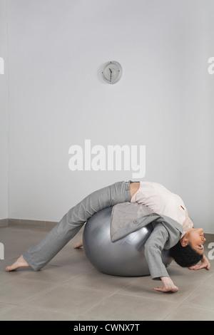 Geschäftsfrau, die Ausübung auf Fitness-Ball im Büro - Stockfoto
