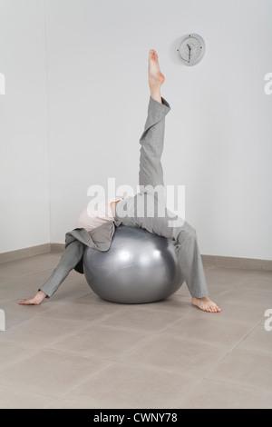 Geschäftsfrau, die Dehnung auf Fitness-Ball im Büro - Stockfoto