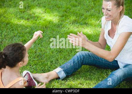 Mutter und Tochter spielen auf Rasen - Stockfoto