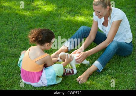 Mutter und Tochter sitzen auf dem Rasen spielen mit Beagle Welpen - Stockfoto