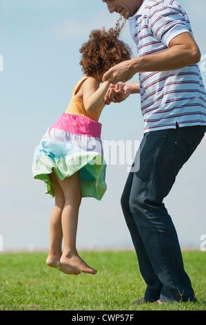 Anhebende Tochter Vater in Luft, Seitenansicht - Stockfoto