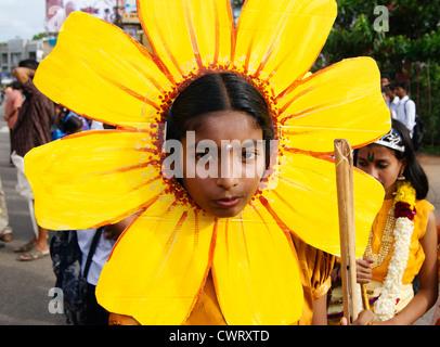 Ein Schulmädchen mit Sonnenblume Modell Thema auf Kopf während der Onam Feier Kulturprogramm Prozession in Kerala - Stockfoto