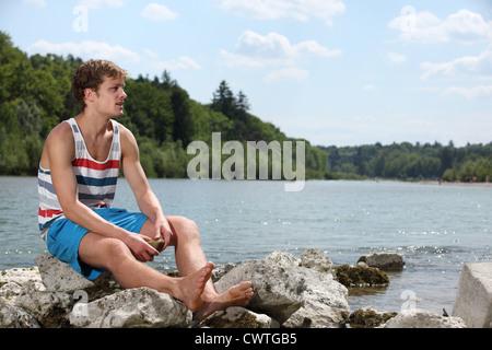 Junger Mann in Sommerkleidung am Fluss Isar, München, Bayern, Deutschland - Stockfoto