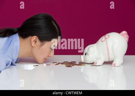 Junge Frau am Tisch mit Sparschwein - Stockfoto
