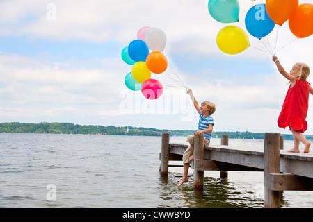 Kinder Luftballons auf hölzerne Pier holding - Stockfoto