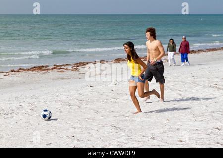 Frauen in Führungspositionen zu sehen Teen paar spielen mit Fußball auf dem weißen Sandstrand von Indian Shores, - Stockfoto