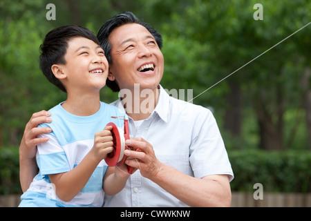 Großvater und Enkel gemeinsam einen Drachen fliegen - Stockfoto