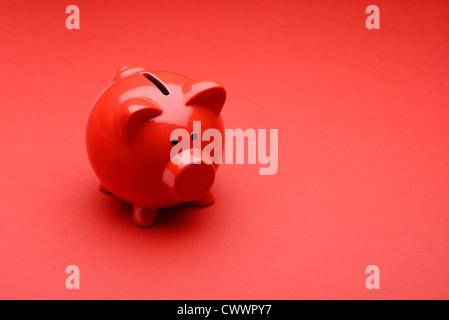 Roten Sparschwein auf rotem Grund - Stockfoto