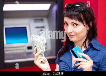 Schöne Frau mit Kreditkarte, sie ist zieht Geld von einem Geldautomaten. - Stockfoto