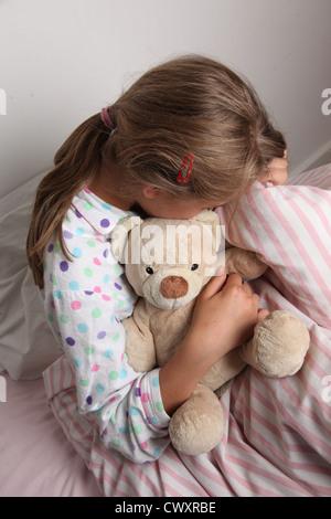 Junges Mädchen im Bett kuscheln einen Teddybär. - Stockfoto