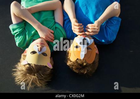 Zwei Jungs tragen Tier Masken auf Rücken liegend