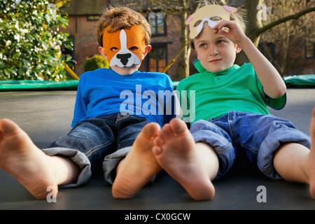Zwei jungen mit Masken auf Trampolin liegen