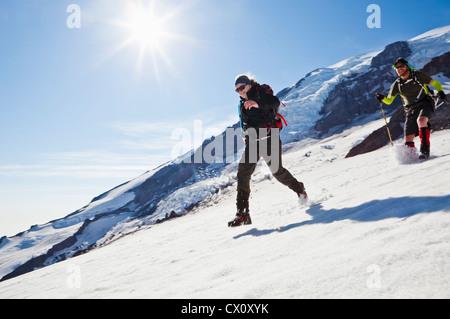 Ein junger Mann und eine Frau laufen und springen nach unten das Schneefeld Muir auf Mount Rainier, Washington, - Stockfoto