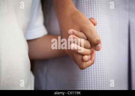 Ältere Schwester hält jüngeren Bruder Hand gehen gemeinsam zur Schule, Close-up - Stockfoto
