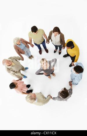 Gruppe von Personen in einem Kreis mit Frau in der Mitte, hoher Winkel Ansicht - Stockfoto