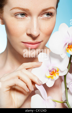 Frau Holding Orchideen - Stockfoto