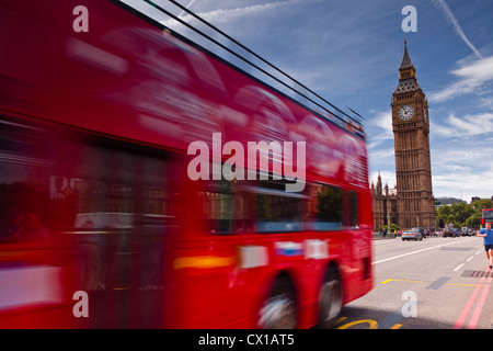 Ein Bus fährt über die Westminster Bridge vorbei an den Houses of Parliament in London. - Stockfoto