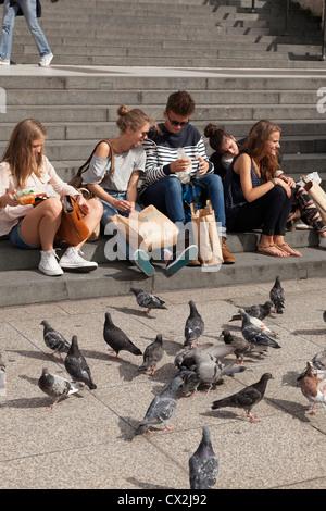 Touristen auf den Stufen der St. Pauls Kathedrale in London die Tauben füttern. - Stockfoto