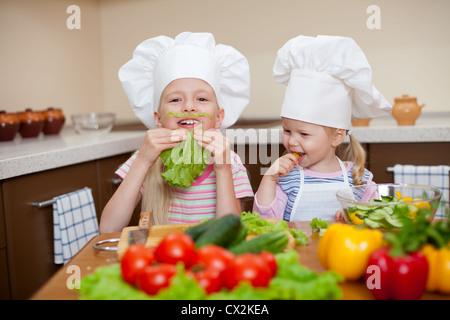 zwei kleine Mädchen, die Zubereitung von gesunden Speisen und viel Spaß in der Küche - Stockfoto