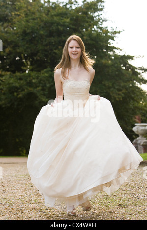 Junge Frau in Creme Brautkleid auf Schotterweg zu Fuß in Richtung der Kamera hält Röcke und lächelnd - Stockfoto